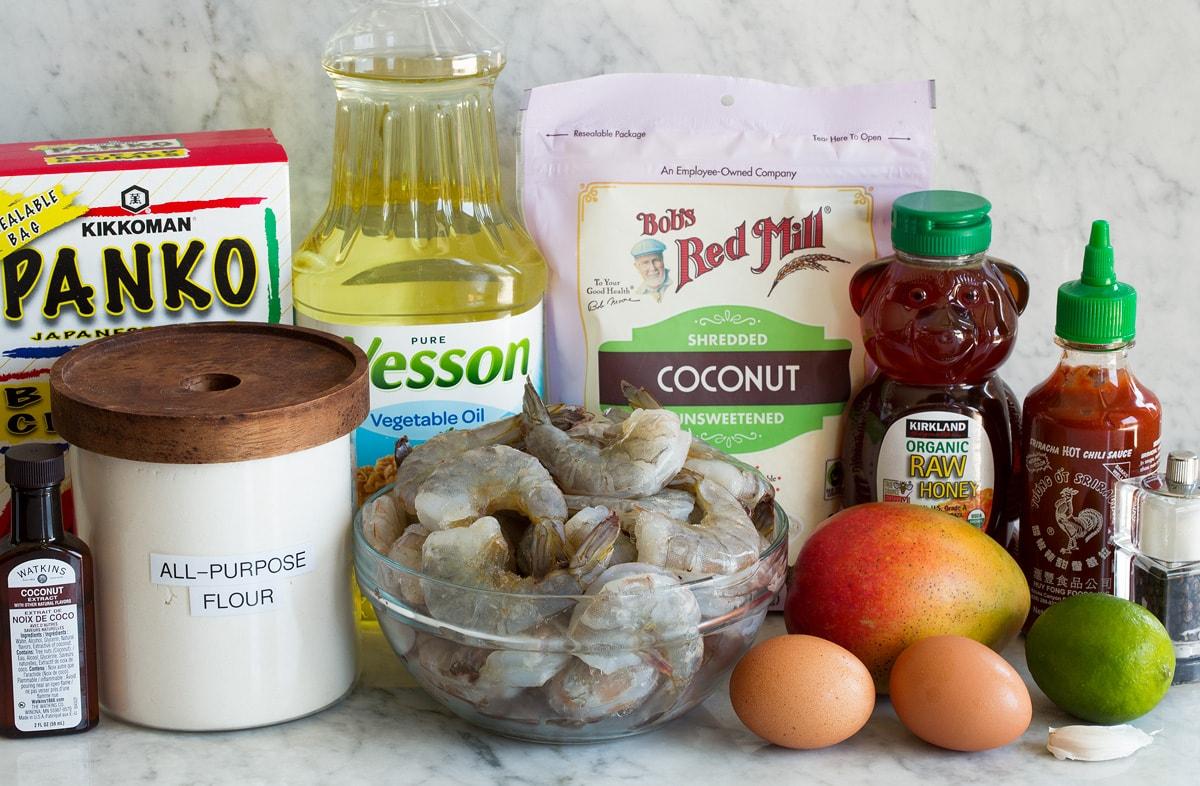 Photo: Ingredients used to make coconut shrimp. Includes shrimp, flour, shredded coconut, panko, eggs, honey, mango, sriracha, lime, coconut extract, salt and pepper.