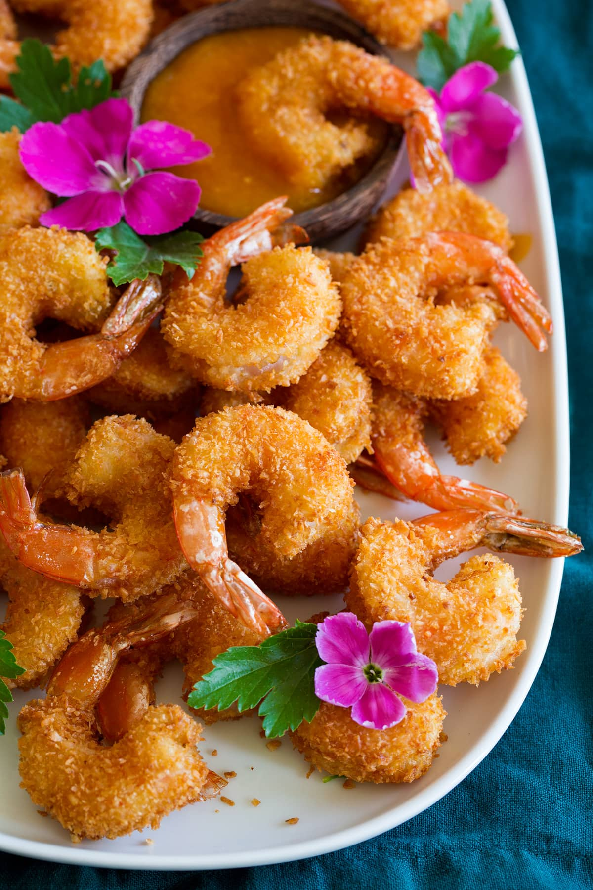Photo: Coconut Shrimp shown close up from a side angle on a platter.