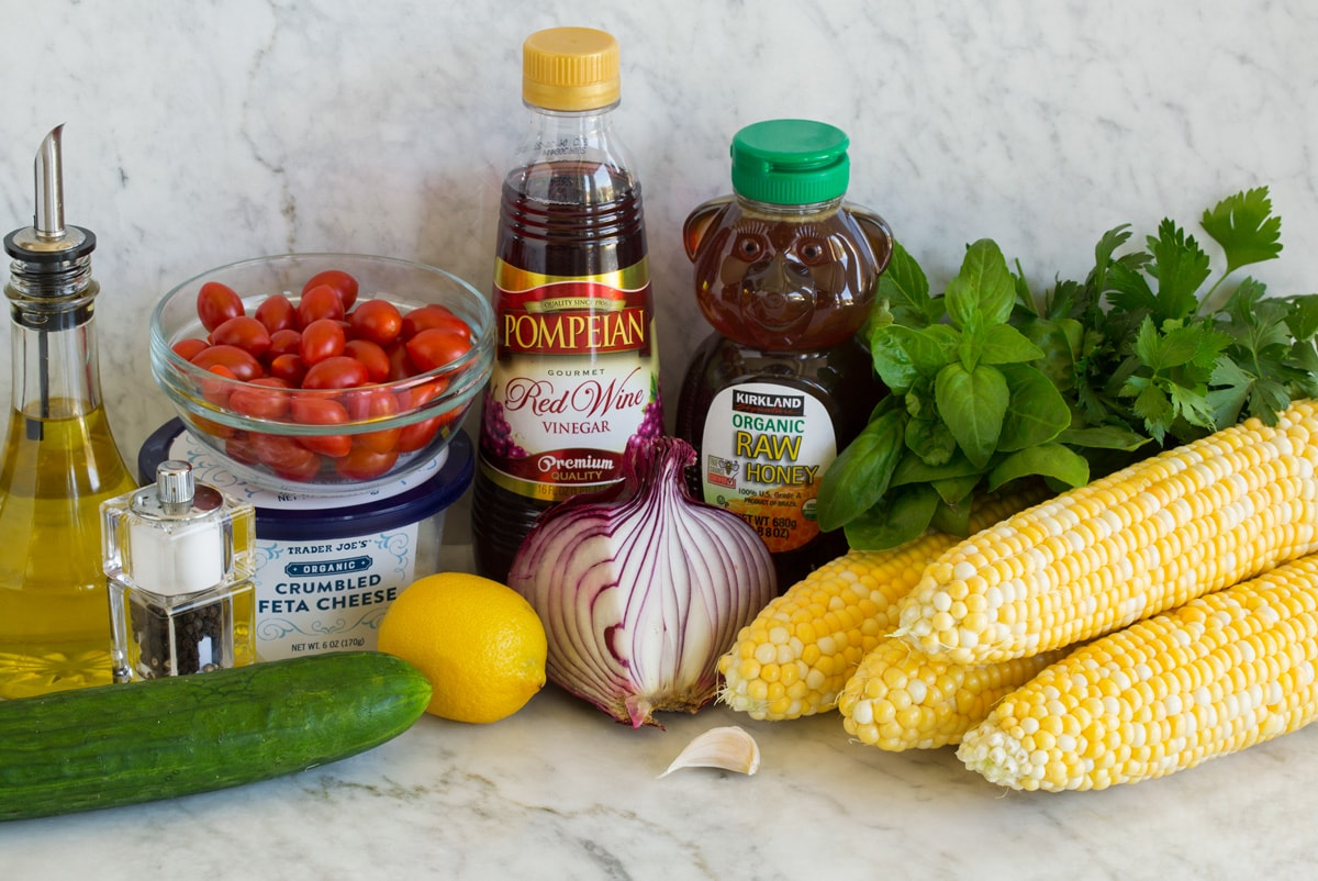 Photo: Ingredients used to make corn salad shown in image. Includes corn on the cob, cucumber, red onion, parsley, basil, tomatoes, feta, red wine vinegar, lemon, honey, olive oil, garlic, salt and pepper.