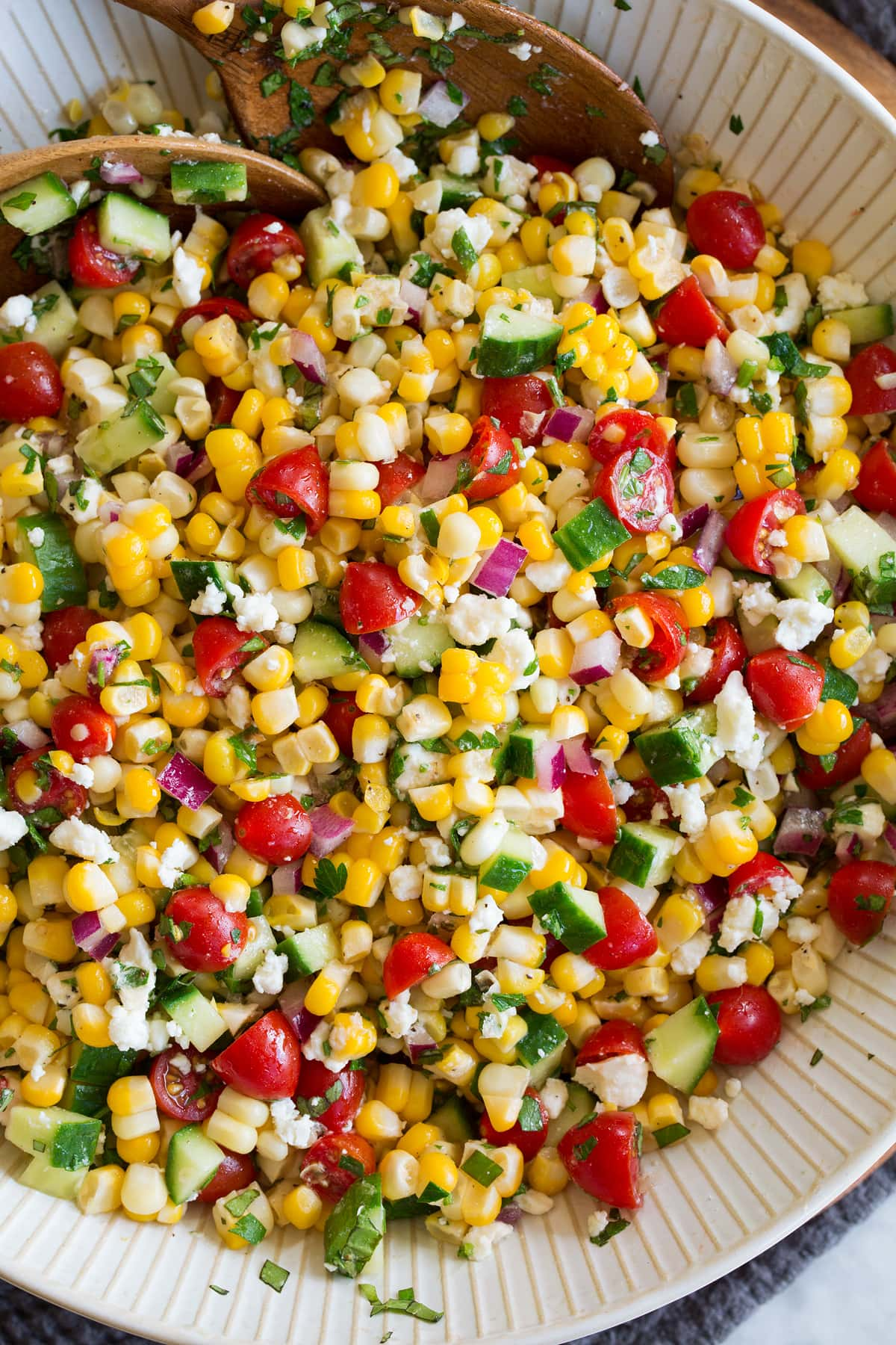 Photo: Corn salad shown close up from above in a serving bowl with wooden serving spoons.