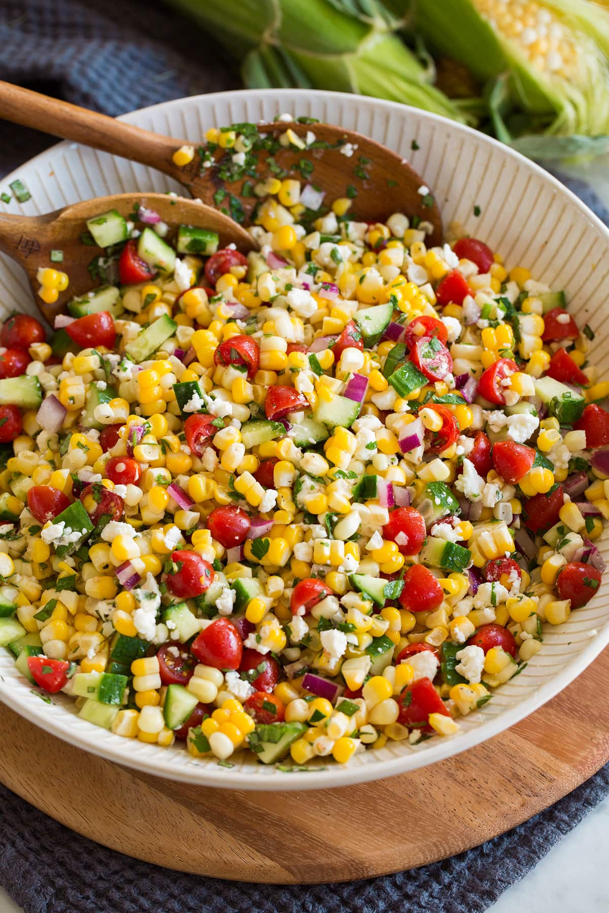 Photo: Corn salad shown in a white serving bowl over a wooden platter and blue cloth. Salad includes fresh corn, tomatoes, red onion, cucumber, feta, herbs and dressing.