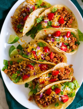 Photo: 7 ground turkey tacos in a row shown on a white oval platter from above. Tacos are filled with meat, tomatoes, lettuce, cheese and red onion.