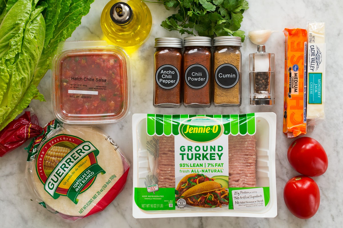 Photo: Ingredients for turkey tacos. Includes ground turkey, corn tortillas, salsa, chili powders, cumin, salt, pepper, garlic, cilantro, tomatoes, cheese, lettuce and olive oil.