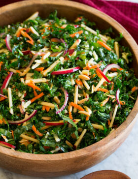 Photo: Kale salad with sliced apples, carrots, red onions, white cheddar and almonds shown in a wooden bowl over a marble surface. A red cloth is shown to the side and wooden salad spoons.