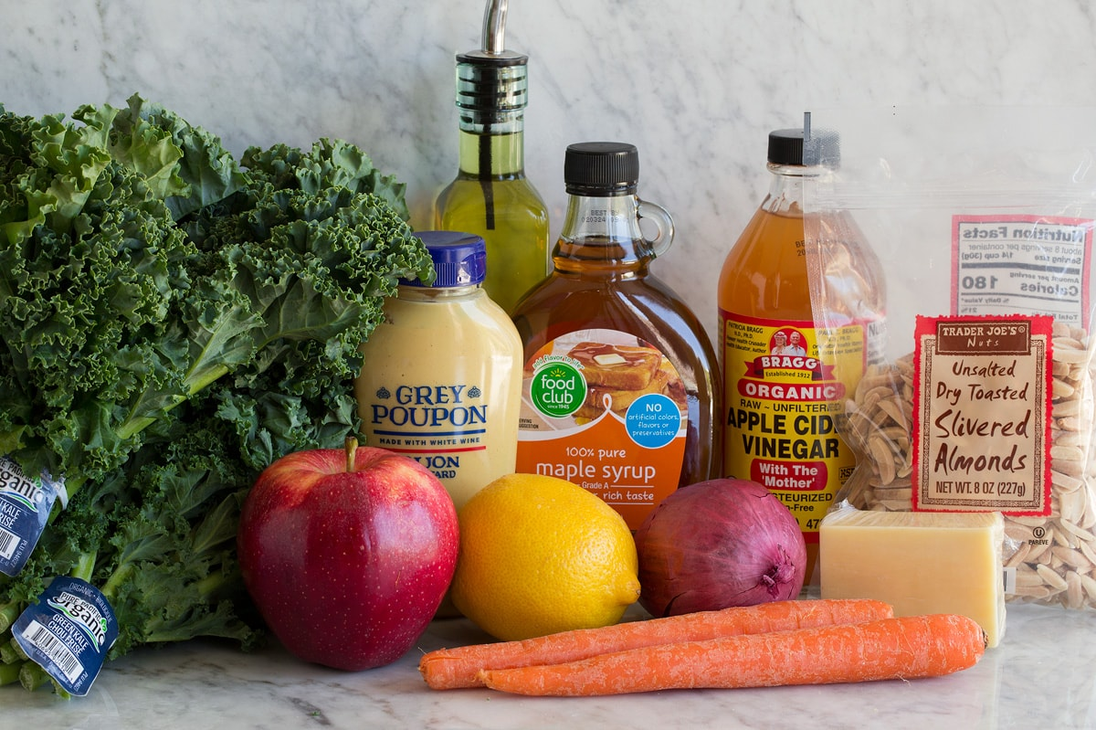 Photo showing ingredients used to make kale salad. Includes kale, apples, lemon, red onion, carrots, white cheddar, maple syrup, apple cider vinegar, dijon mustard, olive oil and slivered almonds.