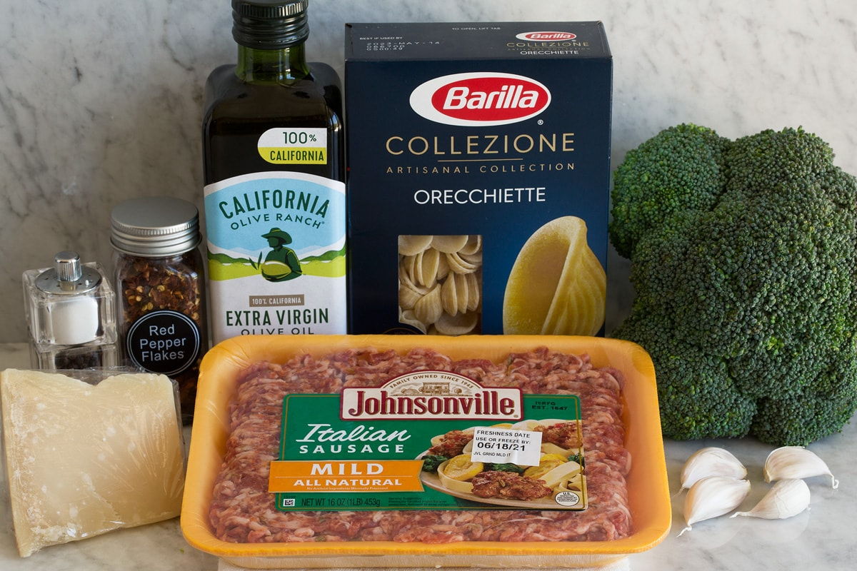 Photo: Ingredients used to make orecchiette with sausage and broccoli shown. Includes Italian sausage, pasta, broccoli, olive oil, garlic, parmesan, red pepper flakes, salt and pepper.