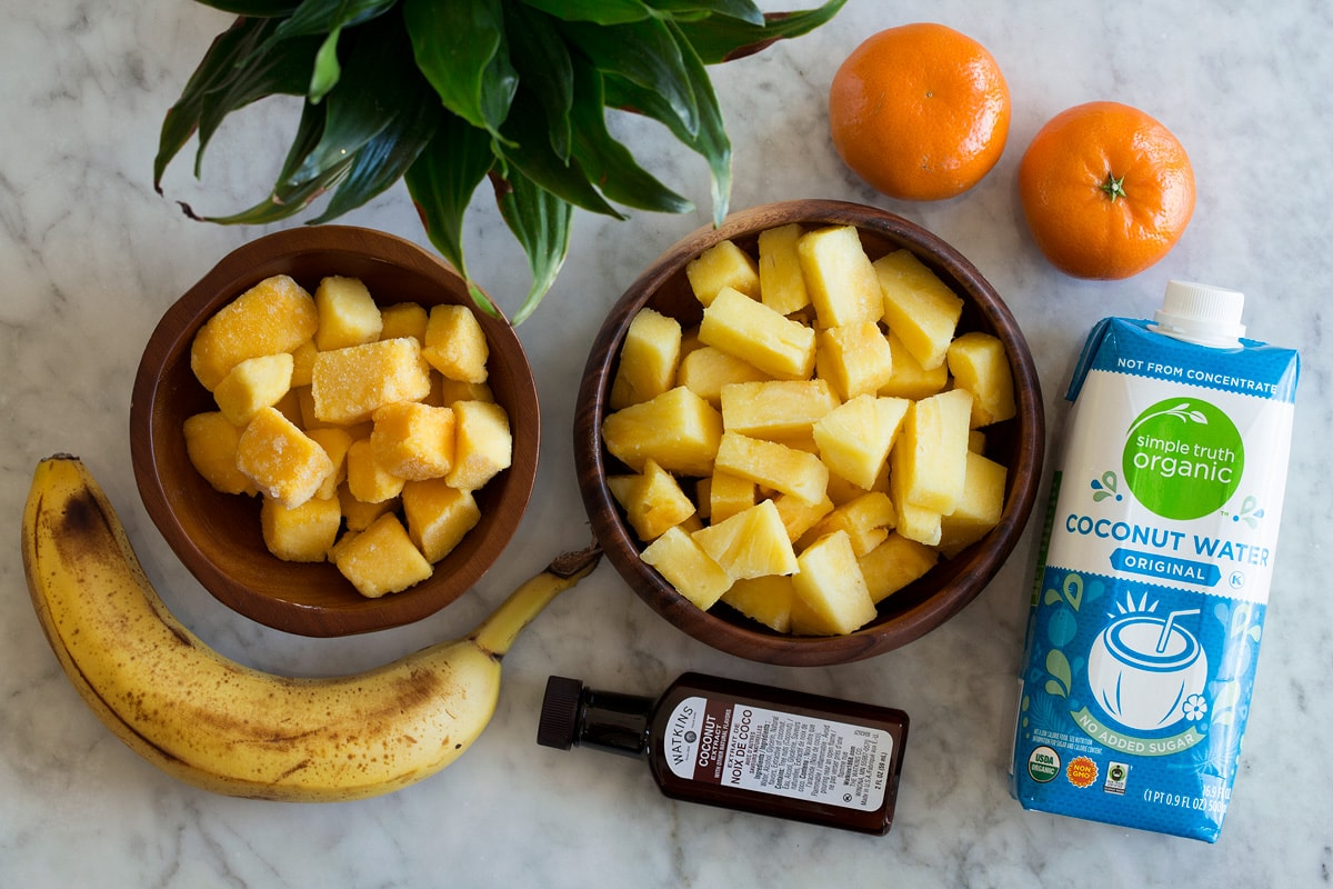 Photo: Ingredients used to make a tropical smoothie shown. Includes pineapple, mangoes, banana, coconut water, clementines, and coconut extract.