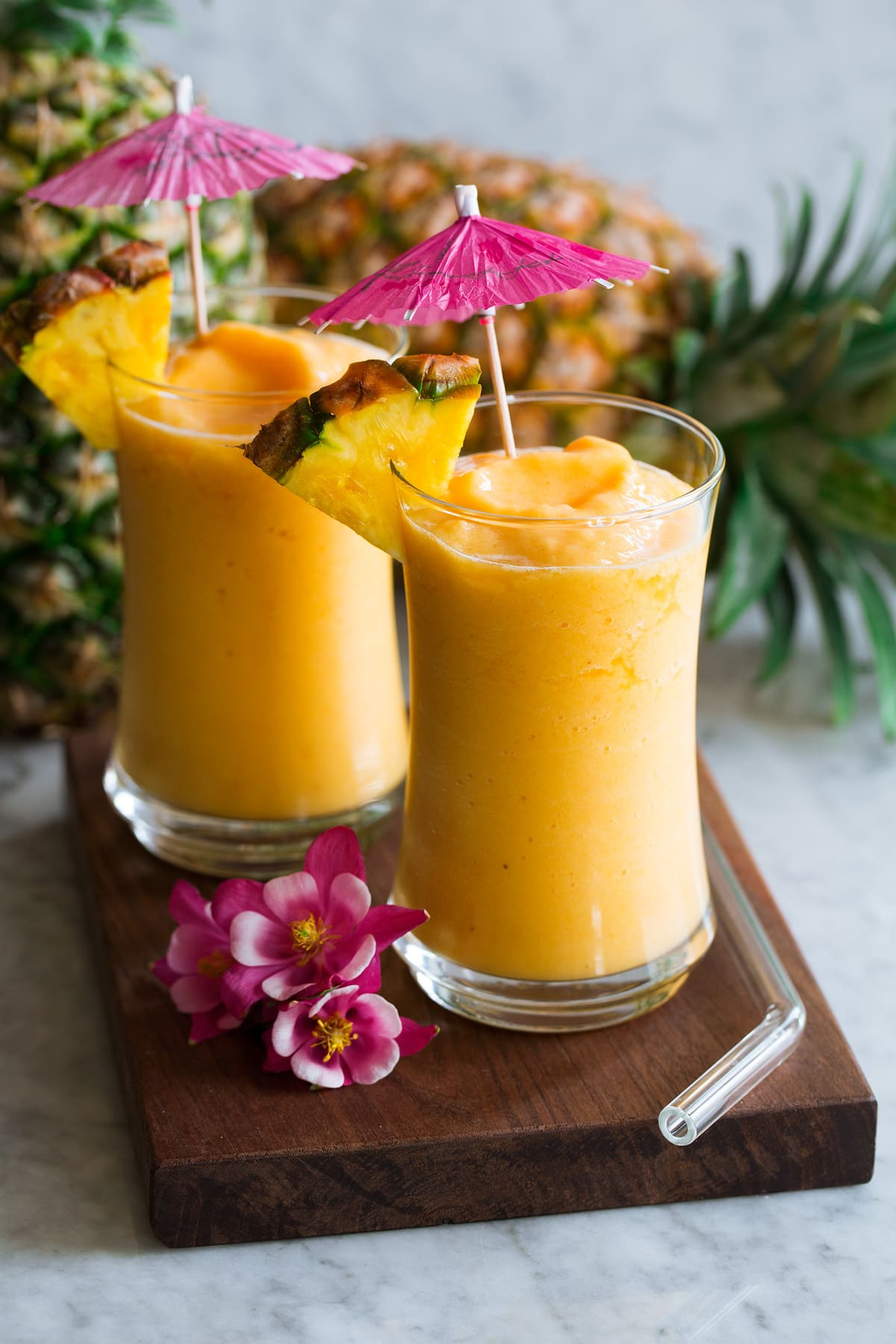Photo: Two tropical smoothies shown in glass cups with pineapple wedges and decorative drink umbrellas for decoration. Tropical flowers are shown to the side and pineapples in the background.