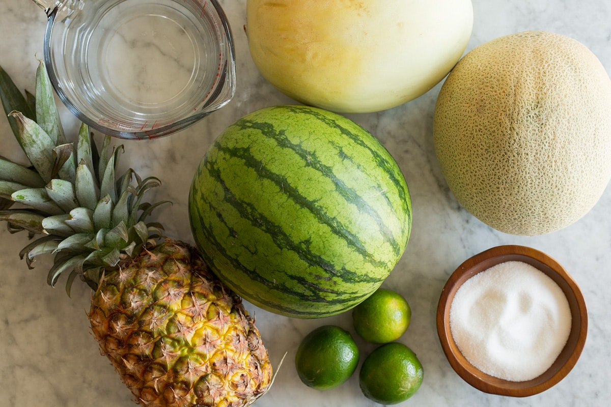 Photo: Ingredients used to make aqua fresca. Includes watermelon, cantaloup, honeydew, pineapple, limes, and sugar.