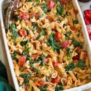 Photo: Baked feta pasta in a white rectangular baking dish shown from a side angle.