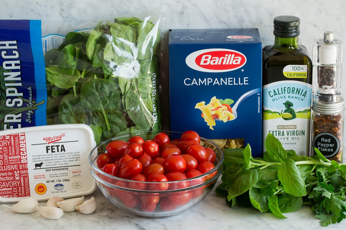 Photo: Ingredients shown that are needed for baked feta pasta. Includes pasta, feta, spinach, basil, parsley, tomatoes, garlic, olive oil, crushed red pepper flakes, salt and pepper.
