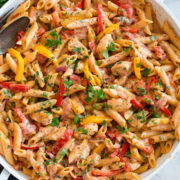 Photo: Creamy cajun chicken pasta shown in a large white pan from overhead.