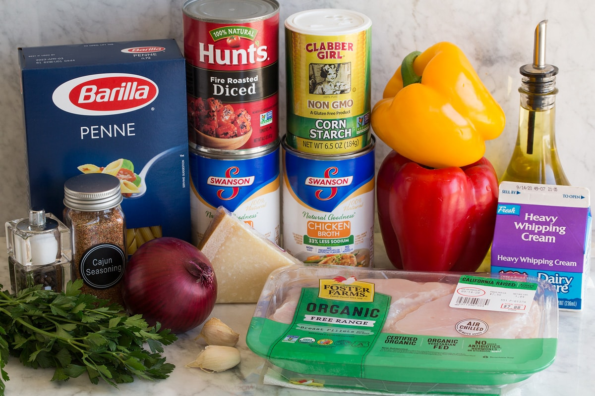 Photo of ingredients. Includes penne pasta, chicken, cream, bell peppers, olive oil, cornstarch, chicken broth, parmesan, tomatoes, red onion, garlic, parsley, salt and pepper.