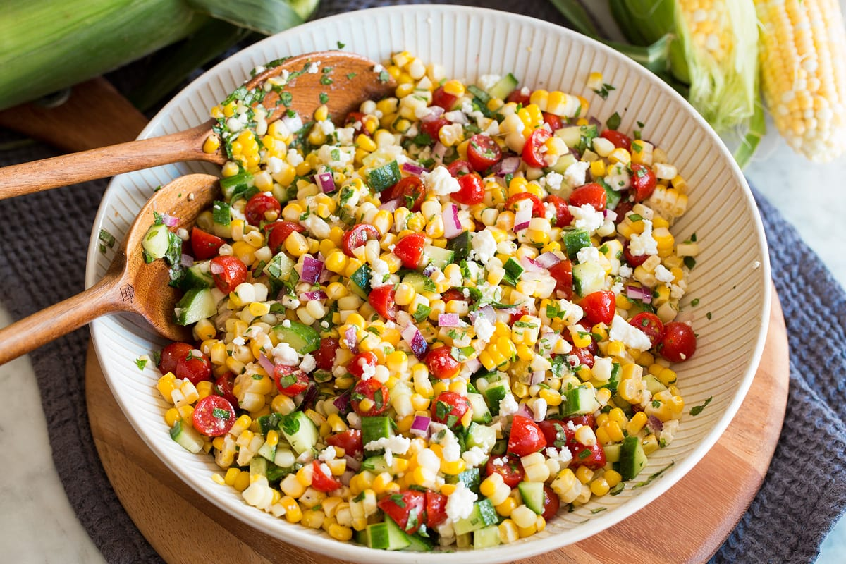 Photo: Completed corn salad after tossing all ingredients and dressing together shown in a white ribbed bowl over a wooden platter.