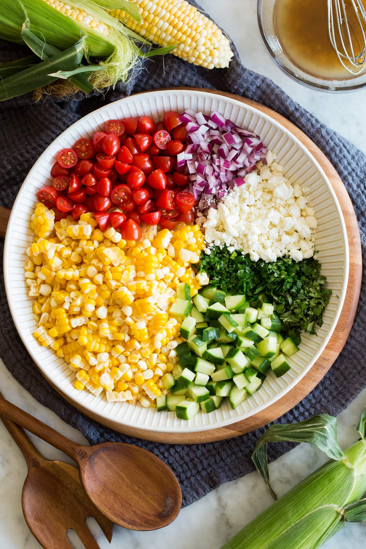 Photo: Corn salad ingredients shown divided into areas before tossing in a bowl. It is shown from above.