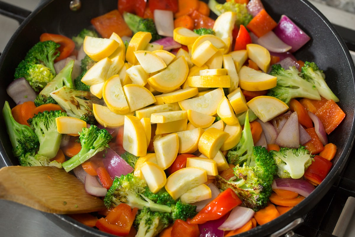 Photo: Adding squash to vegetable mixture in skillet.