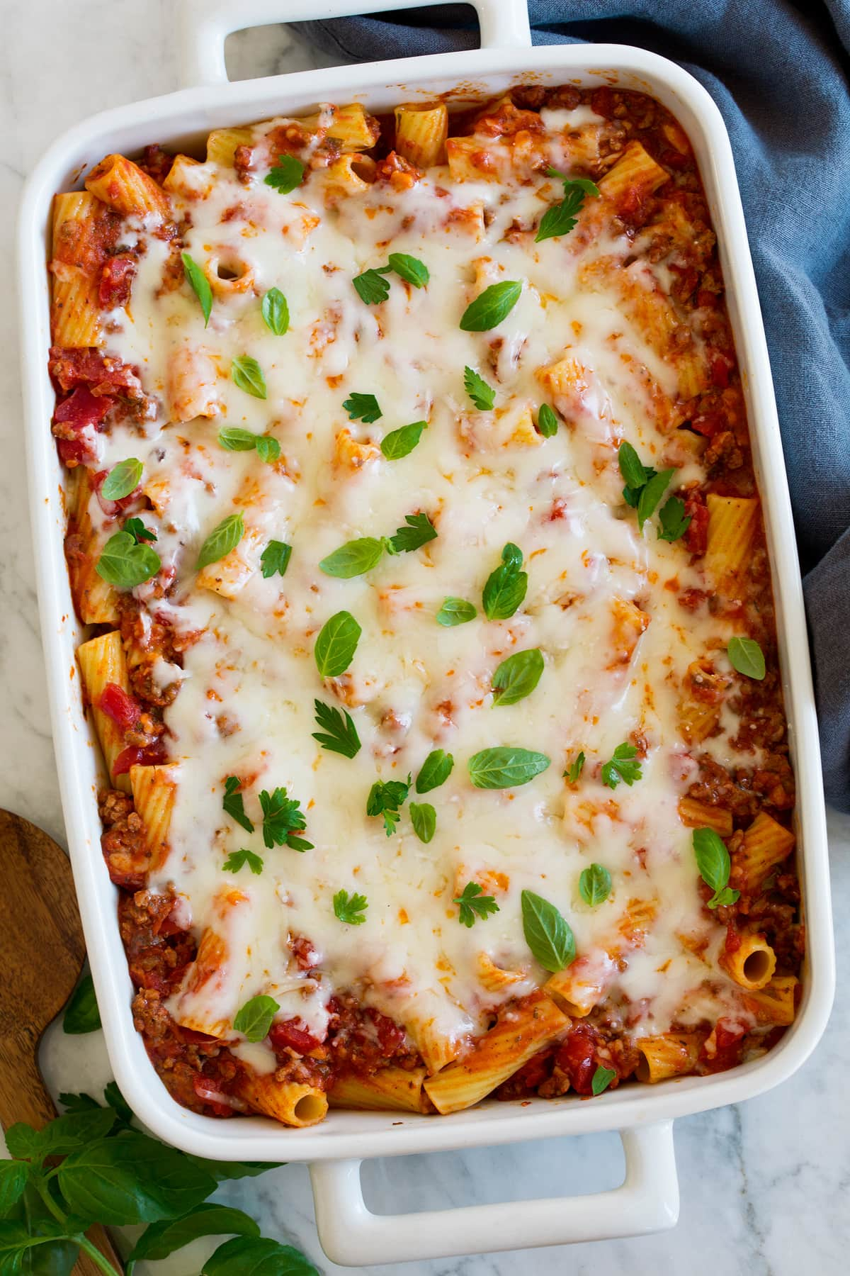 Baked rigatoni shown in a white rectangular ceramic baking dish from above.