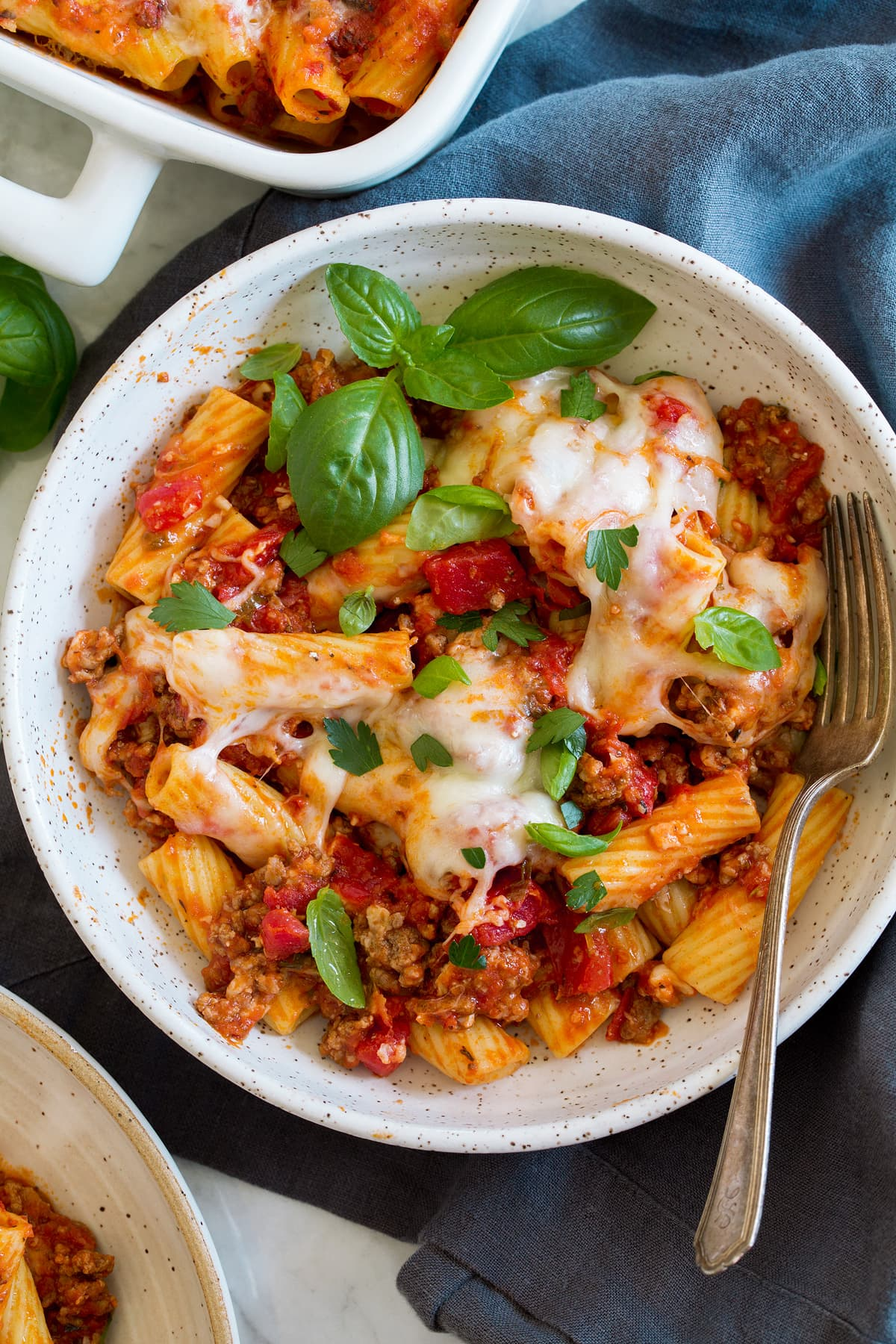 Overhead photo of a serving of baked rigatoni shown in a pasta bowl with a fork.