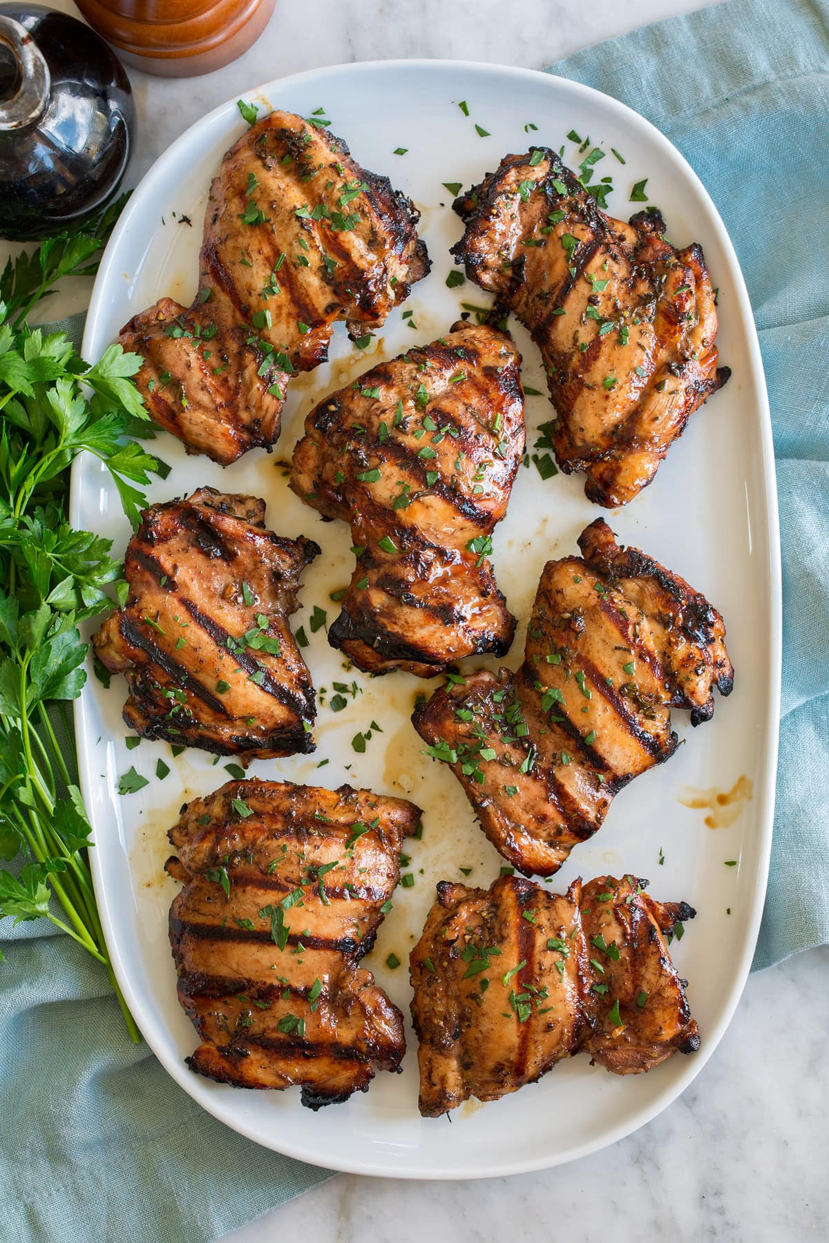 Balsamic chicken thighs shown on an oval white platter from overhead.