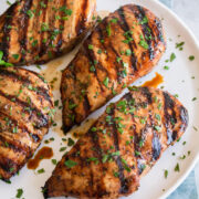Balsamic chicken breasts shown on a white plate over a blue cloth on a marble surface.