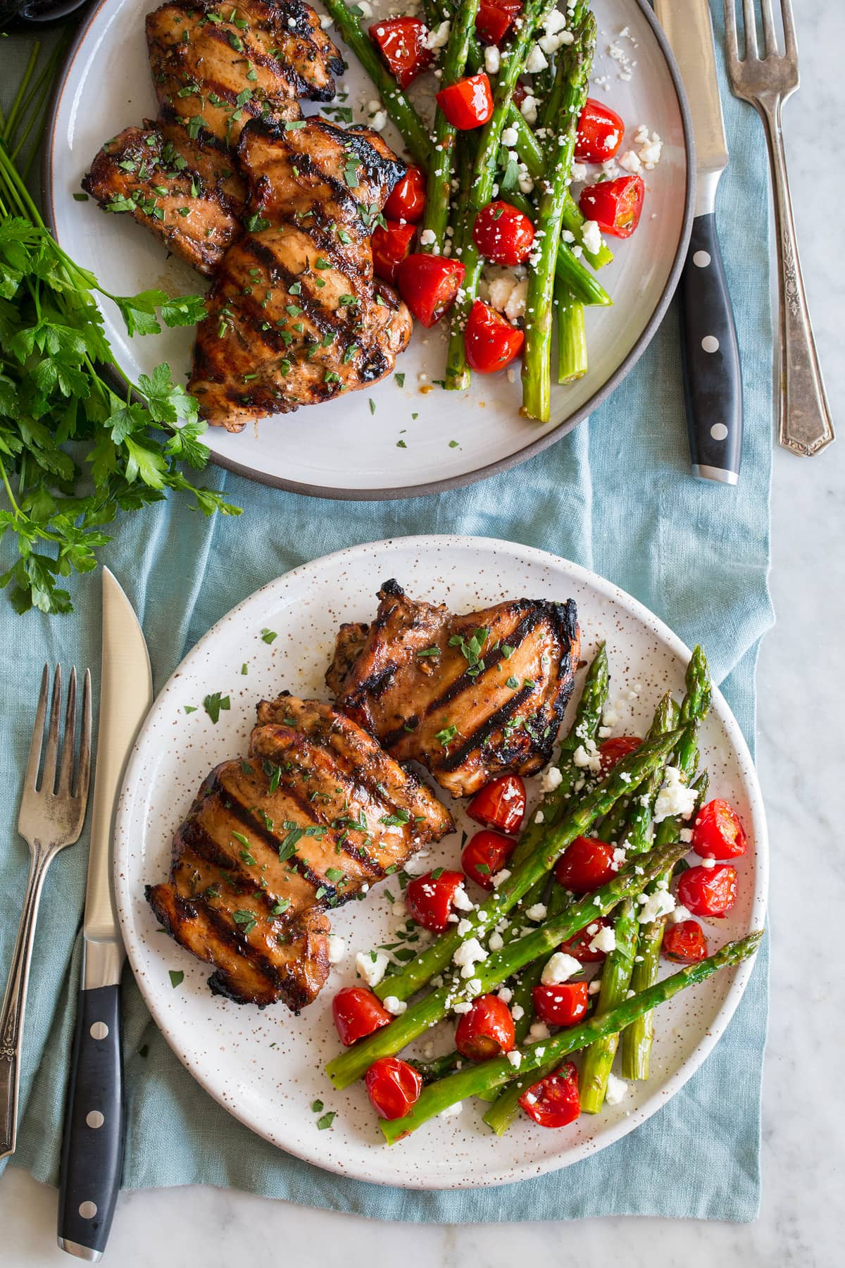 Photo: Two servings of balsamic chicken shown on serving plates with a serving suggestion of roasted asparagus and tomatoes.