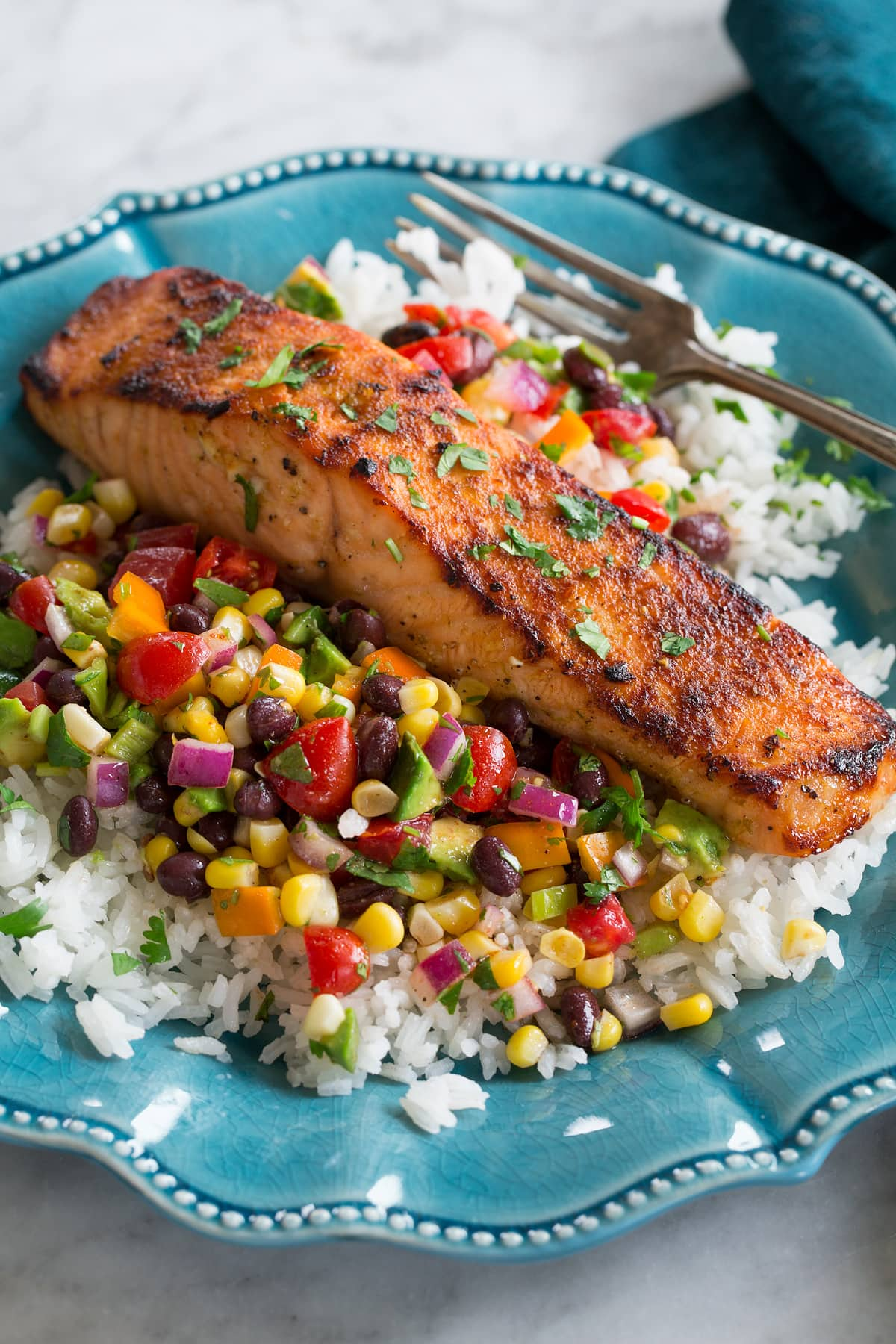 Broiled salmon shown served over a black bean corn salsa and rice on a blue plate.