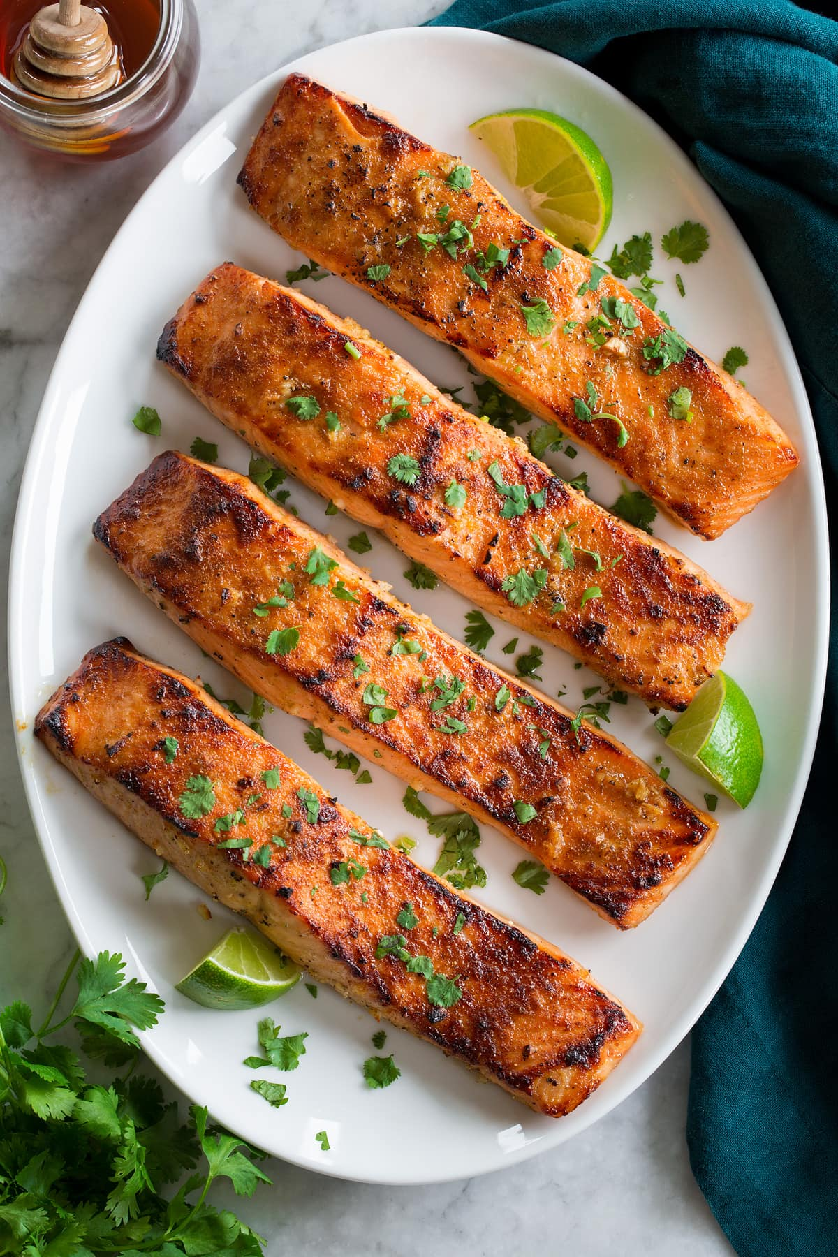 Row of broiled salmon shown from overhead on an a white oval serving platter on a marble surface.