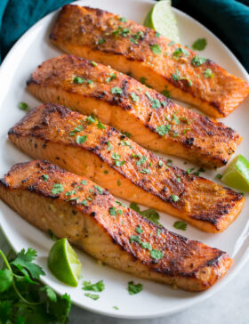 Broiled Salmon shown on a serving platter in a row of four.