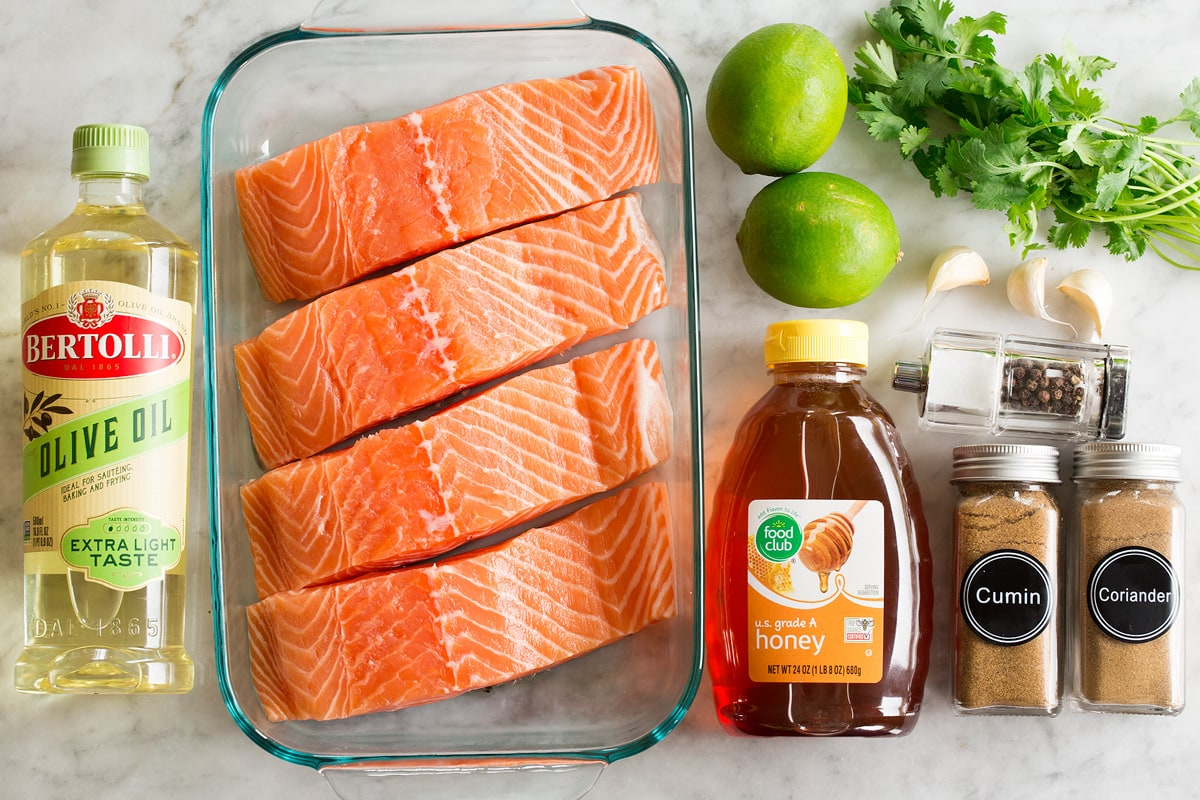 Overhead photo of ingredients used to make broiled salmon with honey, lime, olive oil, garlic, cilantro and spices.