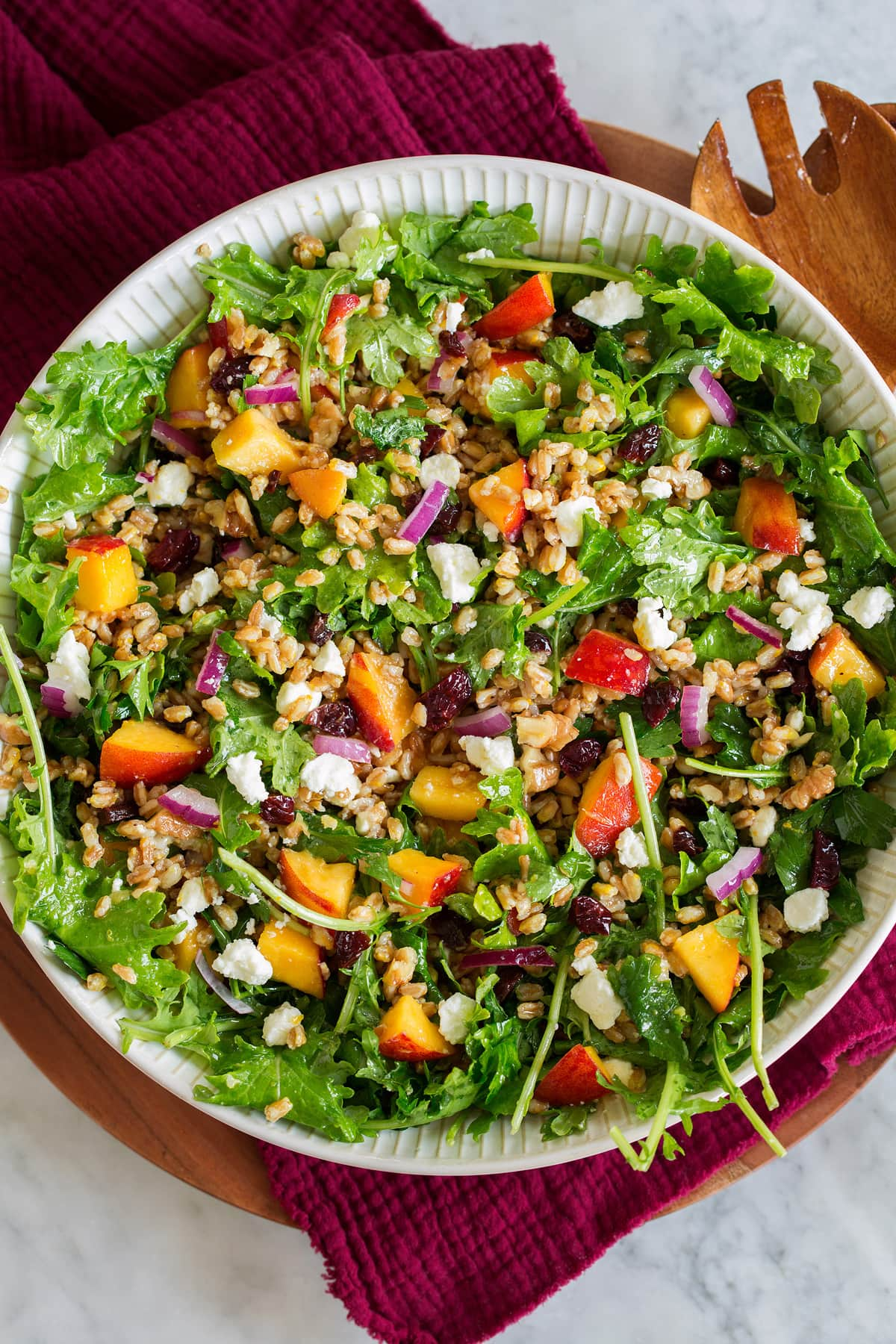 Photo: Farro Salad with peaches, dried cherries, kale, feta and red onion shown in a white serving bowl on a red cloth.