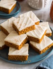 Homemade pumpkin bars stacked on a blue plate.