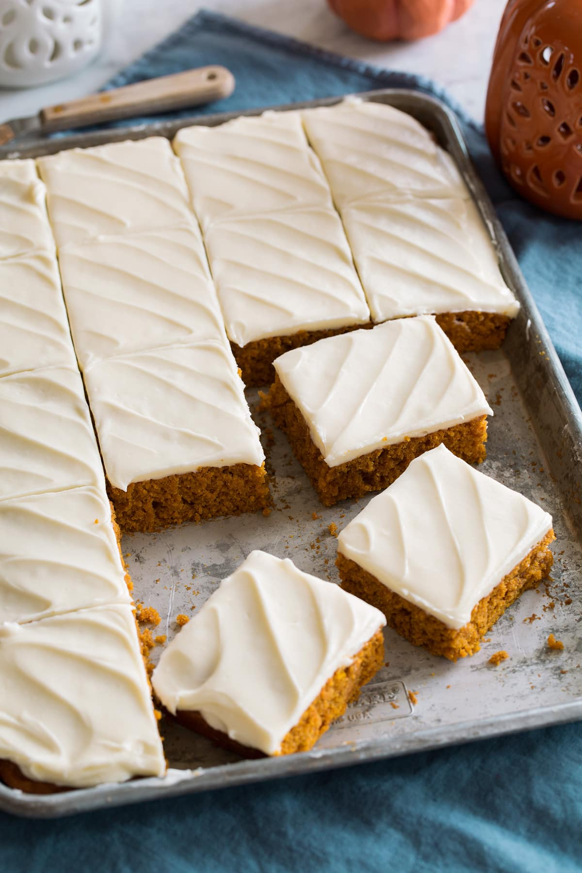 Pumpkin bars with cream cheese frosting cut into squares and shown on a metal sheet pan.