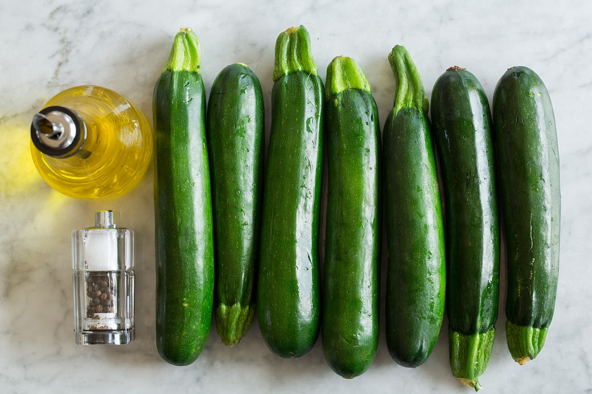 Image of ingredients used to make zucchini noodles. Includes fresh zucchini, olive oil, salt and pepper.