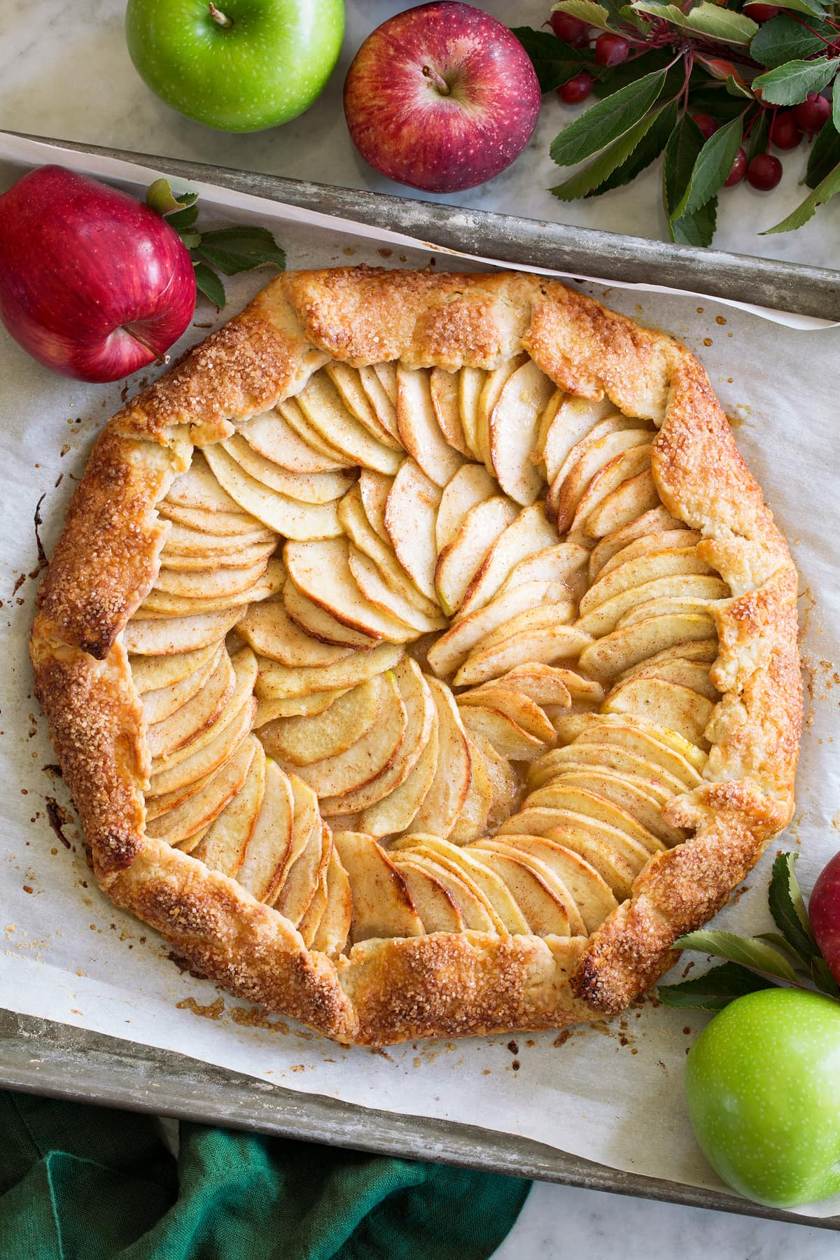 A whole Apple Galette shown from with fresh apples surrounding it.
