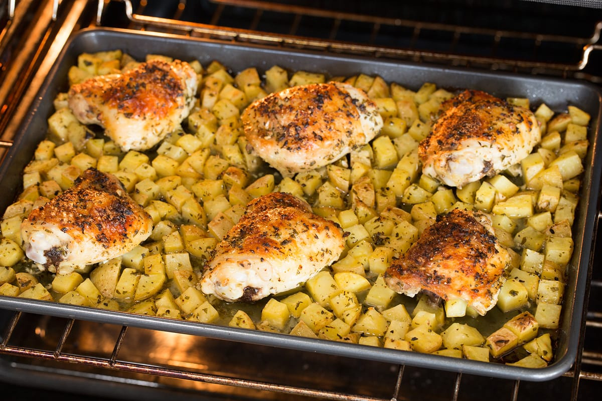 Chicken and potatoes baking in the oven on a baking sheet.