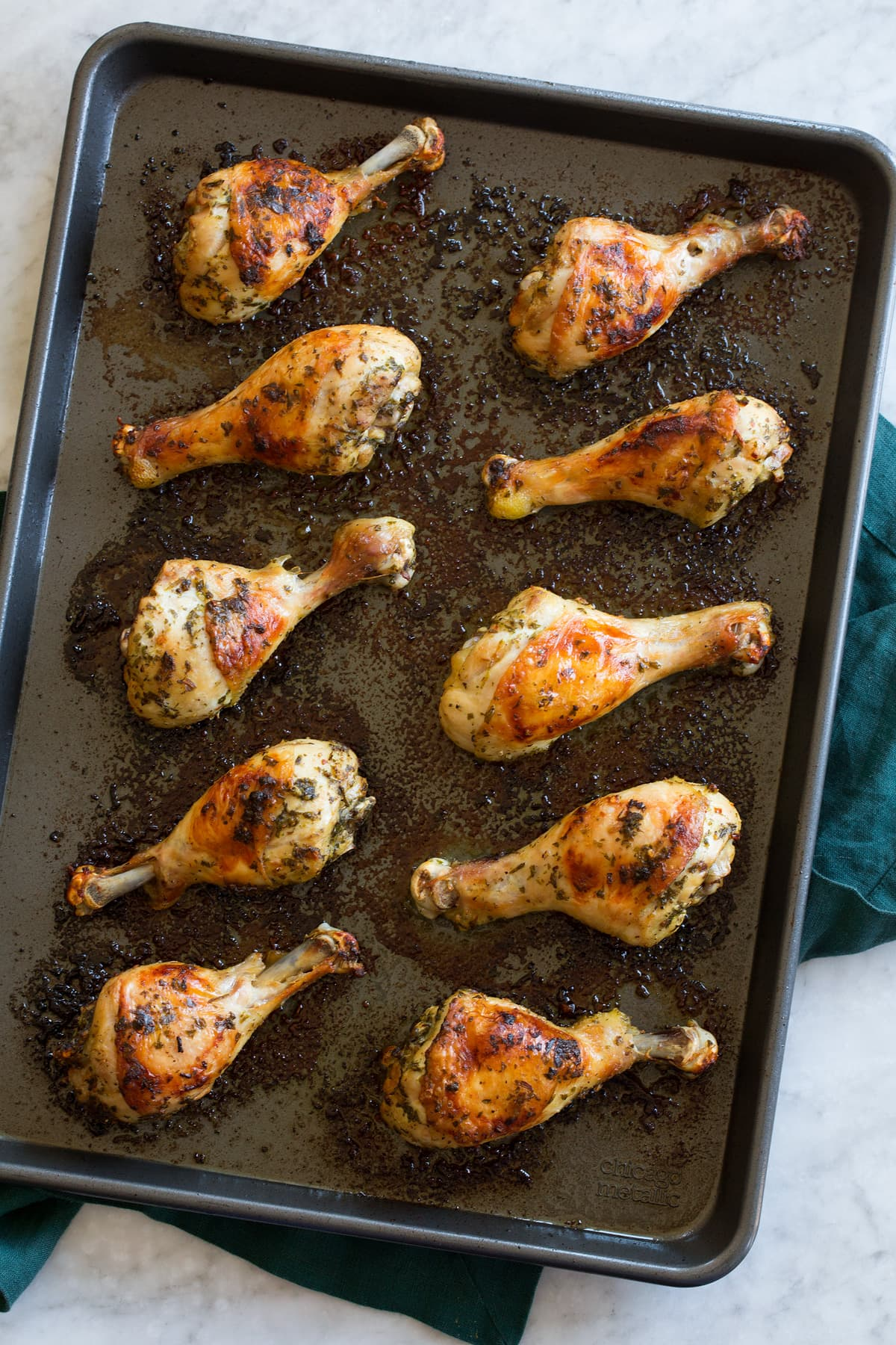 Chicken legs shown on a baking sheet from above, after they're done baking.