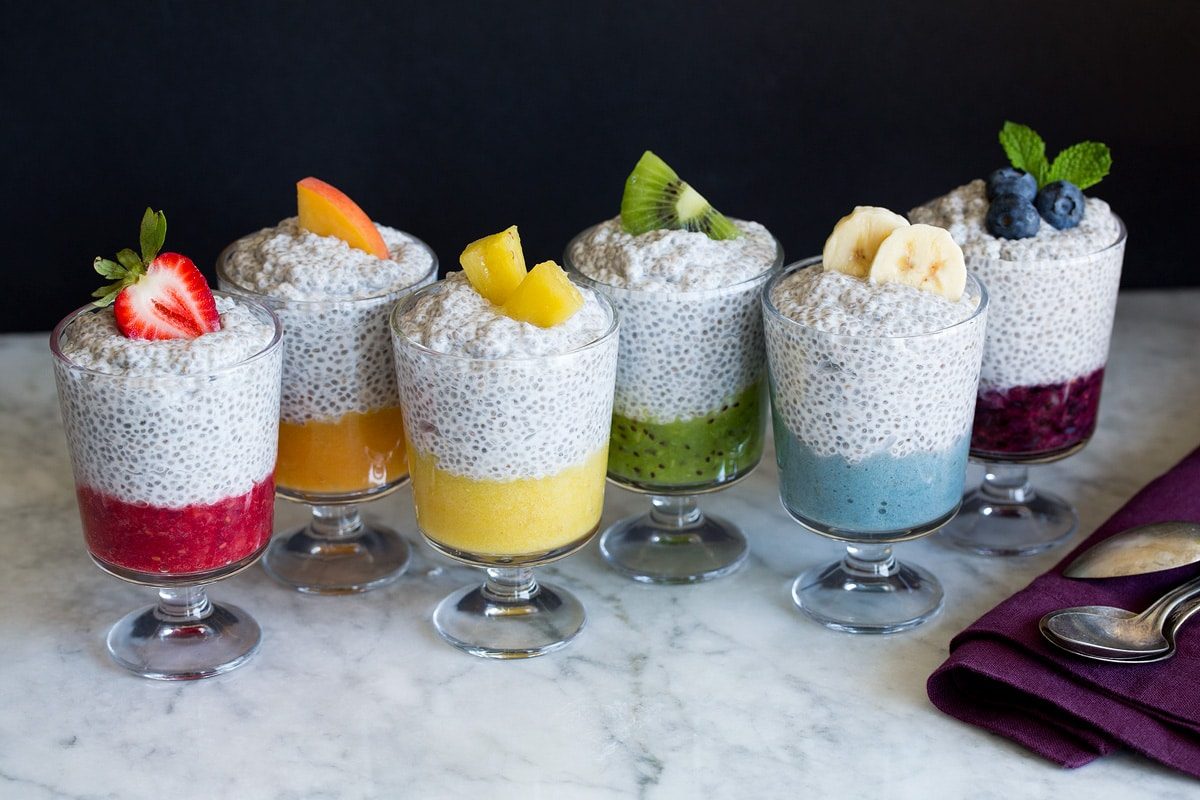 Six jars of chia pudding layered with fruit puree and topped with fresh fruit.
