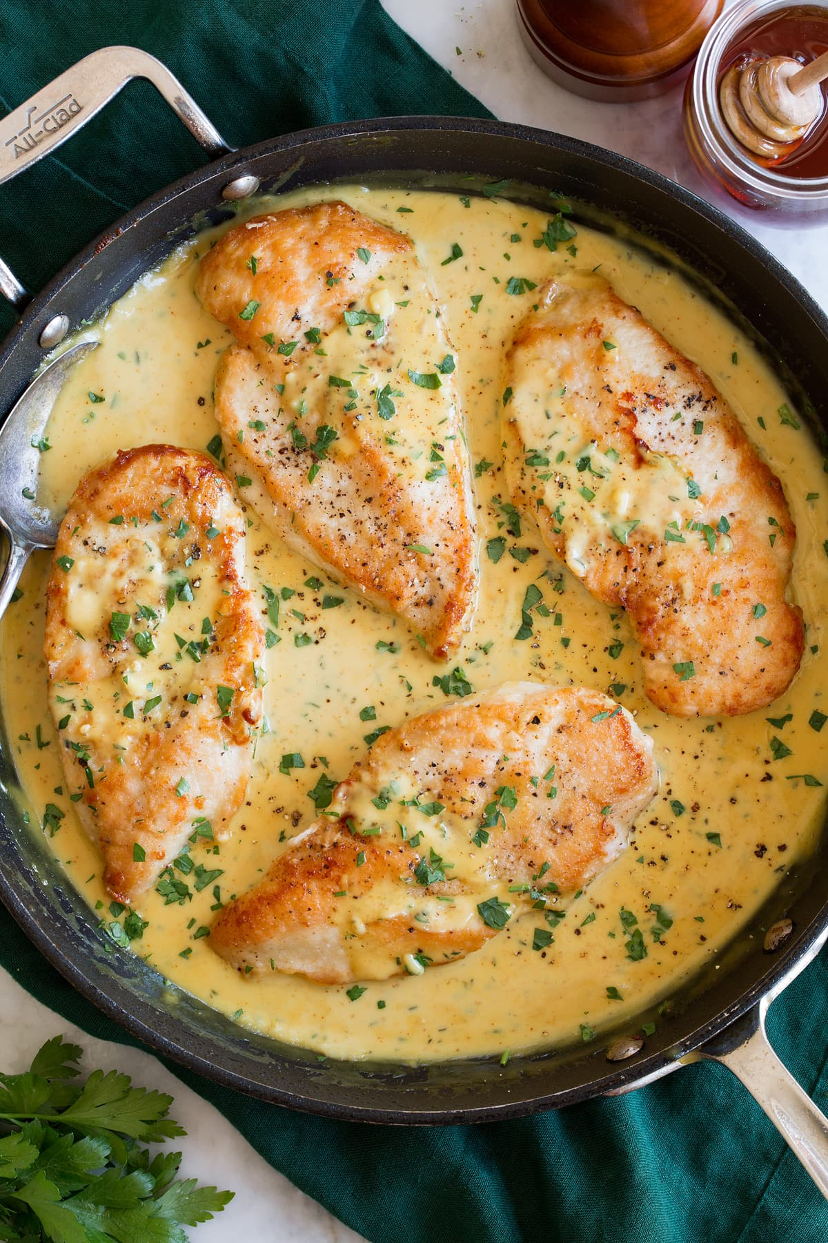 Four chicken breasts in honey mustard sauce in a large black skillet.