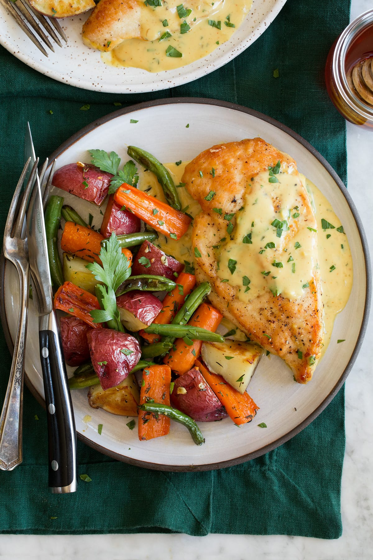 Honey mustard chicken shown with a serving suggestion of roasted vegetables on a serving plate.