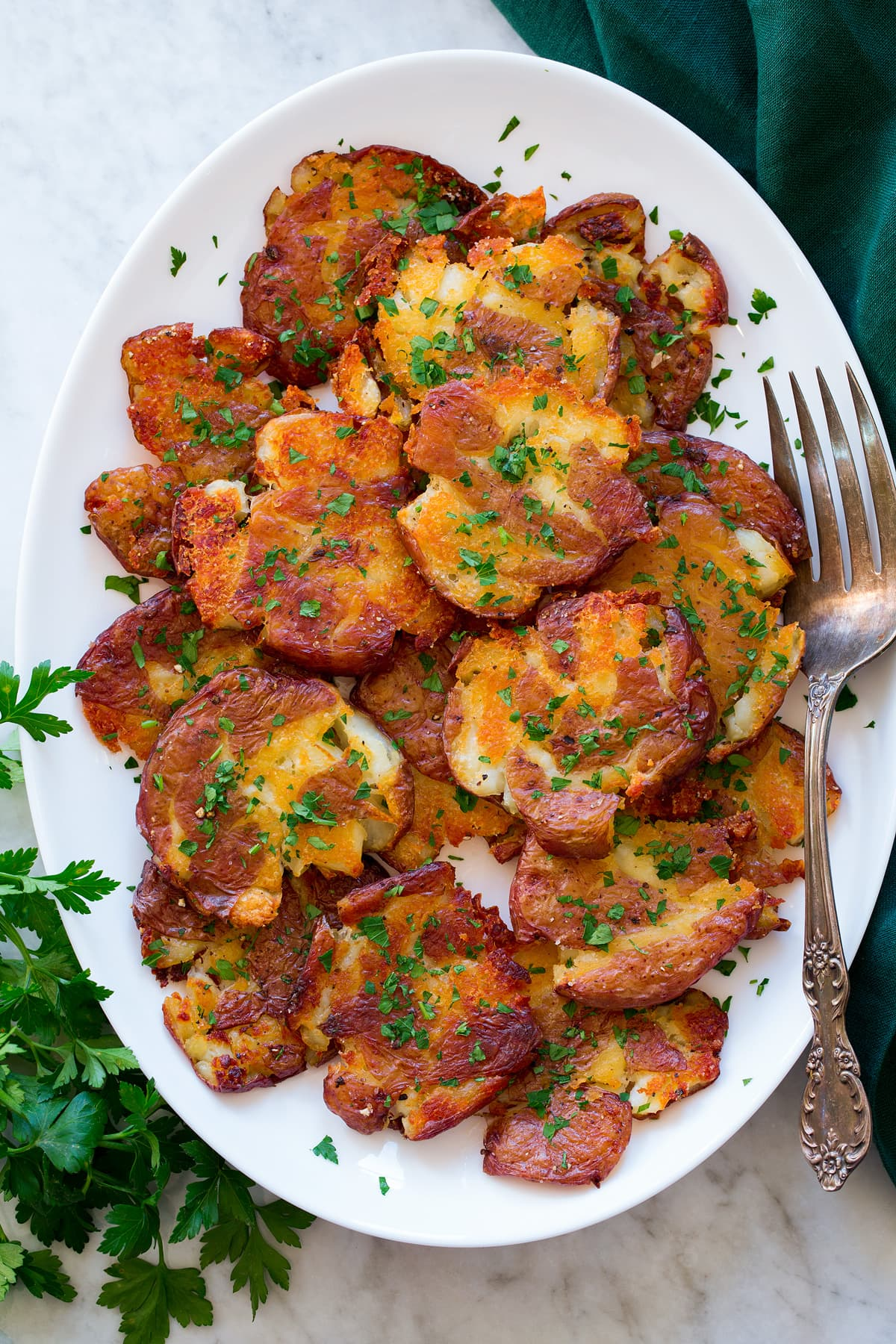 Smashed red potatoes shown piled on a white oval platter. They are shown from above on a white marble surface with a green cloth and parsley to the sides.