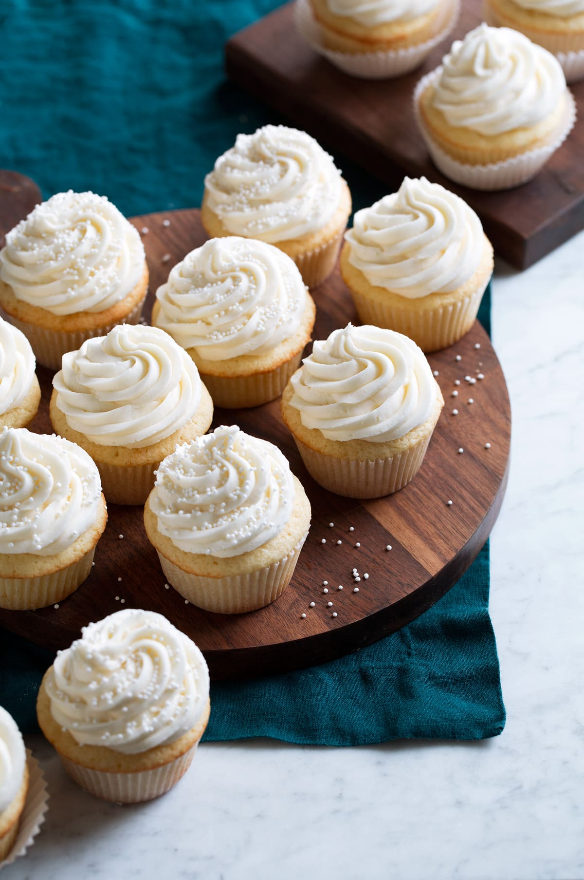 A batch of homemade vanilla cupcakes shown on a wooden serving platter over a blue cloth.