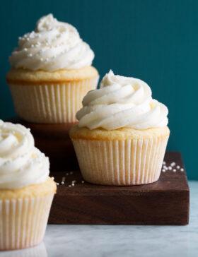Photo of three vanilla cupcakes with vanilla buttercream frosting.
