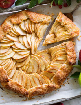 Overhead photo of apple galette with a slice being removed.