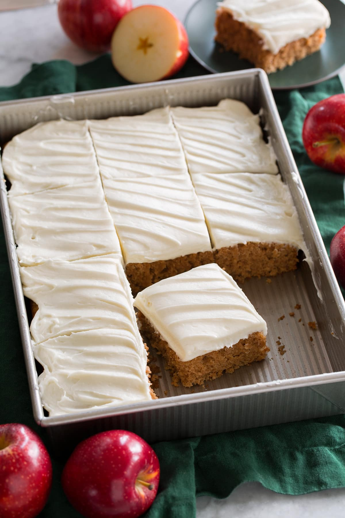 Applesauce cake topped with cream cheese frosting shown in a metal baking sheet over a green cloth.
