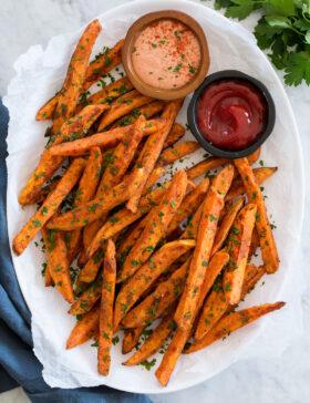 Baked sweet potato fries on a white oval platter with dipping sauces on the side.