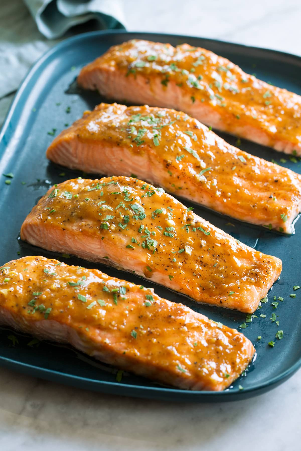 Photo of four salmon fillets coated with a brown sugar glaze resting on a blue rectangular platter on a white marble surface.