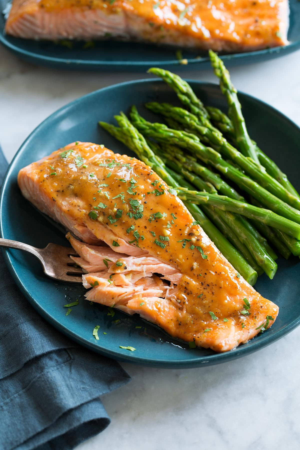Photo of brown sugar salmon with serving suggestion of steamed asparagus. Served on a blue plate with a blue cloth to the side.